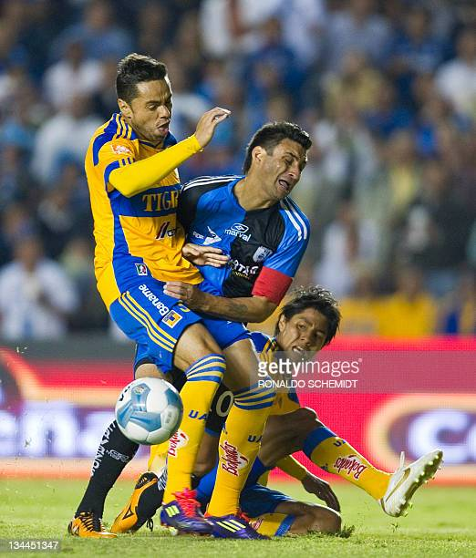 Carlos Bueno of Queretaro vies for the ball with Juninho and Lucas Lobo of Tigres during their Mexican Apertura tournament semifinal in Queretaro on...