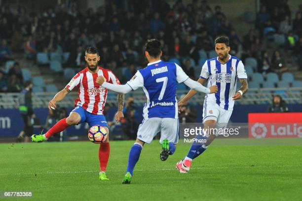 Carlos Carmona of Sporting Gijon duels for the ball with Juanmi of Real Sociedad during the Spanish league football match between Real Sociedad and...