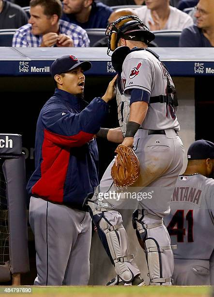 Carlos Carrasco of the Cleveland Indians congratulates teammate Yan Gomes after Gomes heads for the dugout in the seventh inning against the New York...