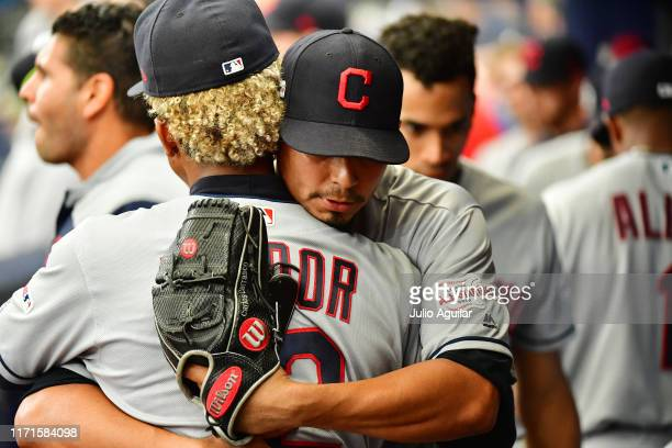 Carlos Carrasco of the Cleveland Indians hugs teammate Francisco Lindor after taking the big league mound for the first time since May 30 at...