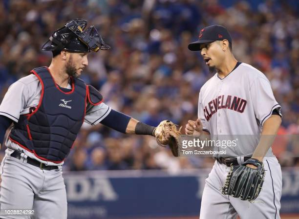 Carlos Carrasco of the Cleveland Indians is congratulated by Yan Gomes after retiring the side in the fourth inning during MLB game action against...