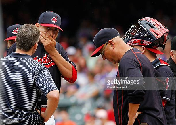 Carlos Carrasco of the Cleveland Indians is is visited at the mound by Manager Terry Francona after being hit by a line drive by Ian Kinsler of the...
