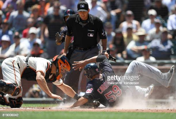 Carlos Carrasco of the Cleveland Indians scores sliding around the tag of Nick Hundley of the San Francisco Giants in the top of the third inning at...
