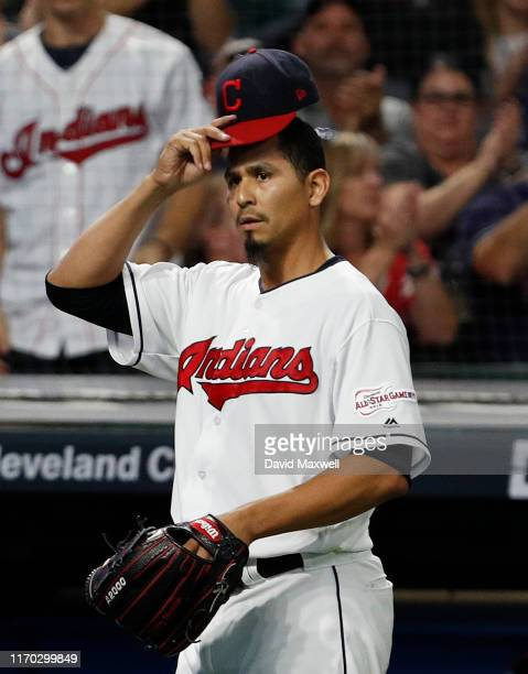 Carlos Carrasco of the Cleveland Indians tips his hat to the crowd as he returns to the dugout after getting J.T. Realmuto of the Philadelphia...