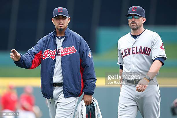 Carlos Carrasco of the Cleveland Indians walks back to the dugout with pitching coach Mickey Callaway before the game against the Cincinnati Reds at...