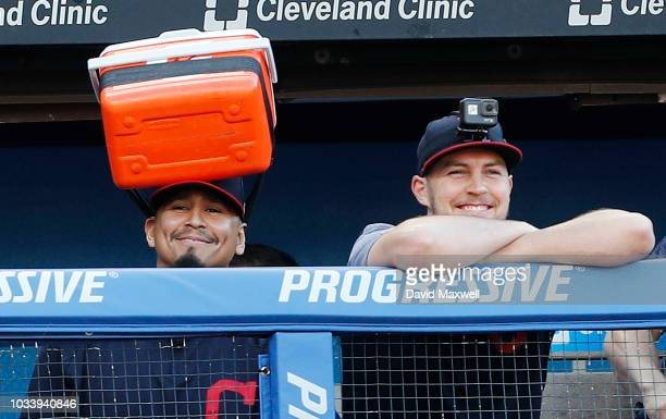 Carlos Carrasco of the Cleveland Indians wears a cooler on his head as he stands in the dugout next to teammateTrevor Bauer during the ninth inning...