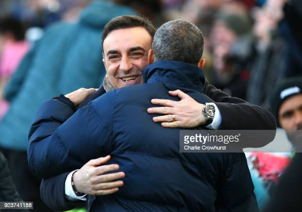 Carlos Carvalhal Manager of Swansea City and Chris Hughton Manager of Brighton and Hove Albion embrace ahead of the Premier League match between...