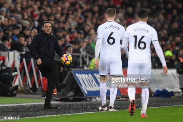 Carlos Carvalhal Manager of Swansea City kicks the ball to Alfie Mawson of Swansea City during the Premier League match between Swansea City and...