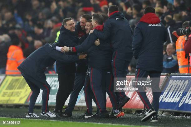 Carlos Carvalhal the manager of Swansea City celebrates with his support staff after his sides third goal during the Premier League match between...