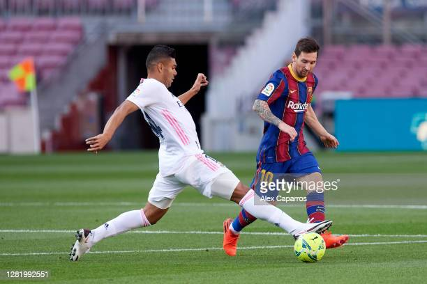 Carlos Casemiro of Real Madrid CF challenges Lionel Messi of FC Barcelona during the La Liga Santander match between FC Barcelona and Real Madrid at...