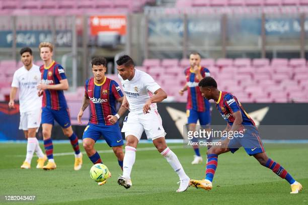Carlos Casemiro of Real Madrid CF plays the ball under pressure from Philippe Coutinho and Ansu Fati of FC Barcelona during the La Liga Santander...
