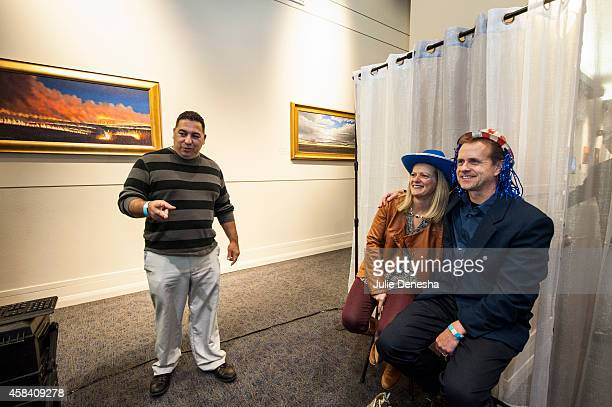 Carlos Ceballos of Candid KC Photobooth encourages Margie and Mark Schroeder of Minneapolis to pose for a photograph at a watch party for Independent...