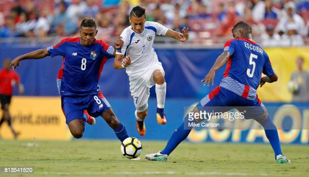 Carlos Chavarra of Nicaragua attempts to split the defense of Edgar Barcenas and Fidel Escobar of Panama during the second half of the CONCACAF Group...