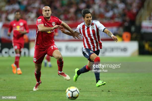 Carlos Cisneros of Chivas fights for the ball with Aurelien Collin of New York RB during the semifinal match between Chivas and New York RB as part...