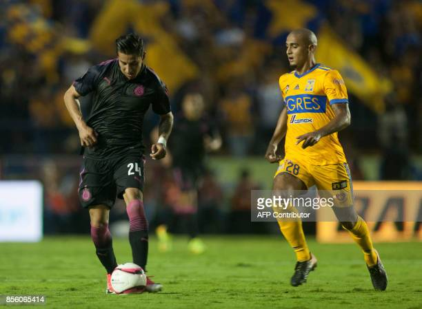 Carlos Cisneros of Chivas is marked by Luis Rodriguez of Tigres during their Mexican Apertura football tournament match at the Universitario stadium...