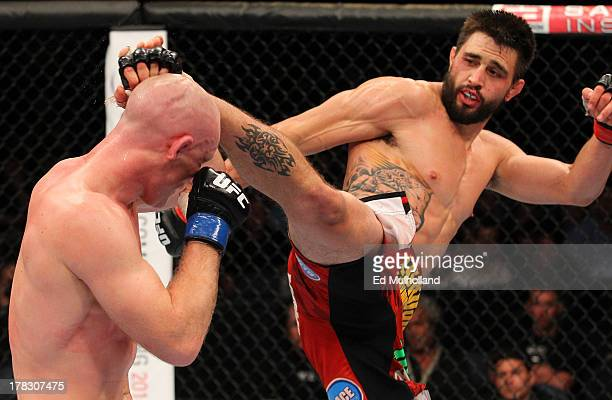 Carlos Condit kicks Martin Kampmann in their welterweight fight during the UFC on FOX Sports 1 event at Bankers Life Fieldhouse on August 28, 2013 in...