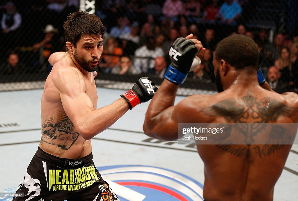 Carlos Condit punches Tyron Woodley in their welterweight bout at UFC 171 inside American Airlines Center on March 15, 2014 in Dallas, Texas.