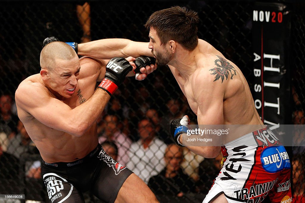 Carlos Condit (R) thorws a punch against Georges St-Pierre in their welterweight title bout during UFC 154 on November 17, 2012 at the Bell Centre in Montreal, Canada.