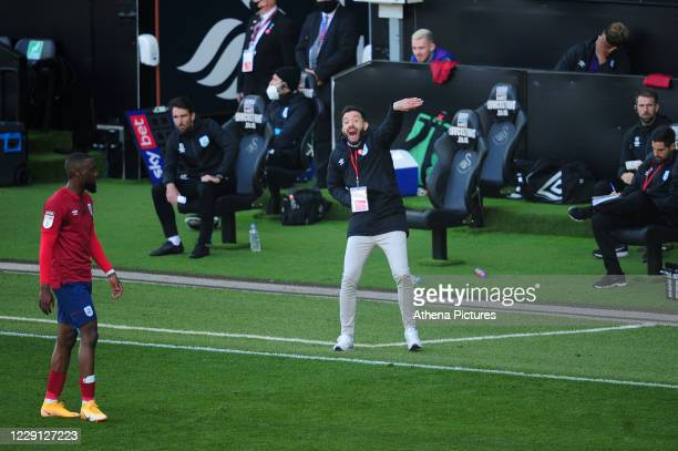 Carlos Corberán Manager of Huddersfield Town shouts instructions to his team from the dugout during the Sky Bet Championship match between Swansea...