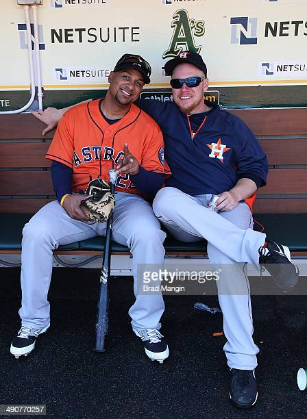 Carlos Corporan and Brett Oberholtzer of the Houston Astros get ready in the dugout before the game against the Oakland Athletics at Oco Coliseum on...
