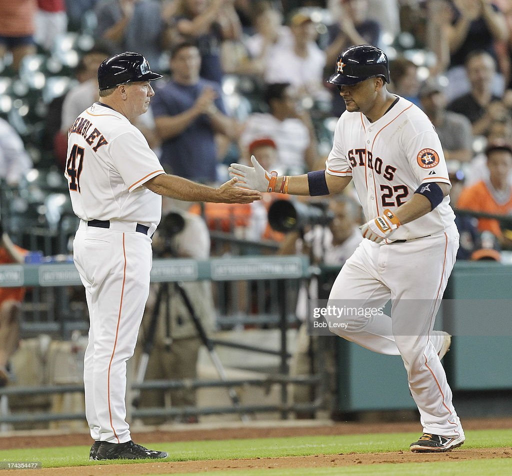 Carlos Corporan #22 of the Houston Astros is congratulated by third base coach Dave Trembley after hitting a two-run home run in the sixth inning against the Oakland Athletics at Minute Maid Park on July 24, 2013 in Houston, Texas.
