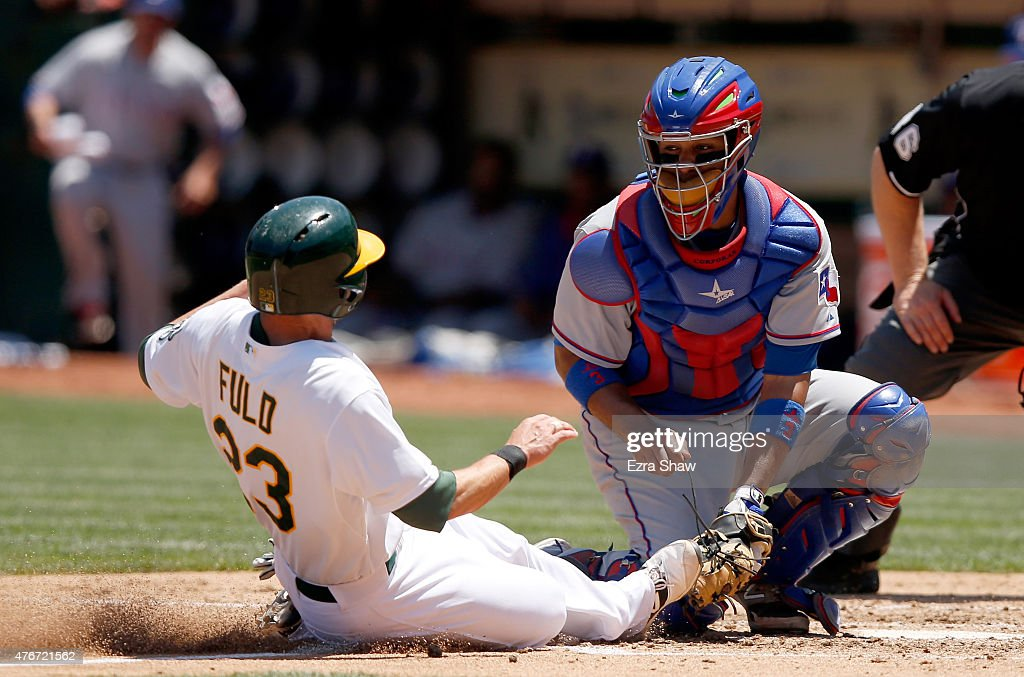 Carlos Corporan #3 of the Texas Rangers tags out Sam Fuld #23 of the Oakland Athletics as he tries to score from third base on a fly-out hit by Josh Reddick #22 in the fifth inning at O.co Coliseum on June 11, 2015 in Oakland, California.