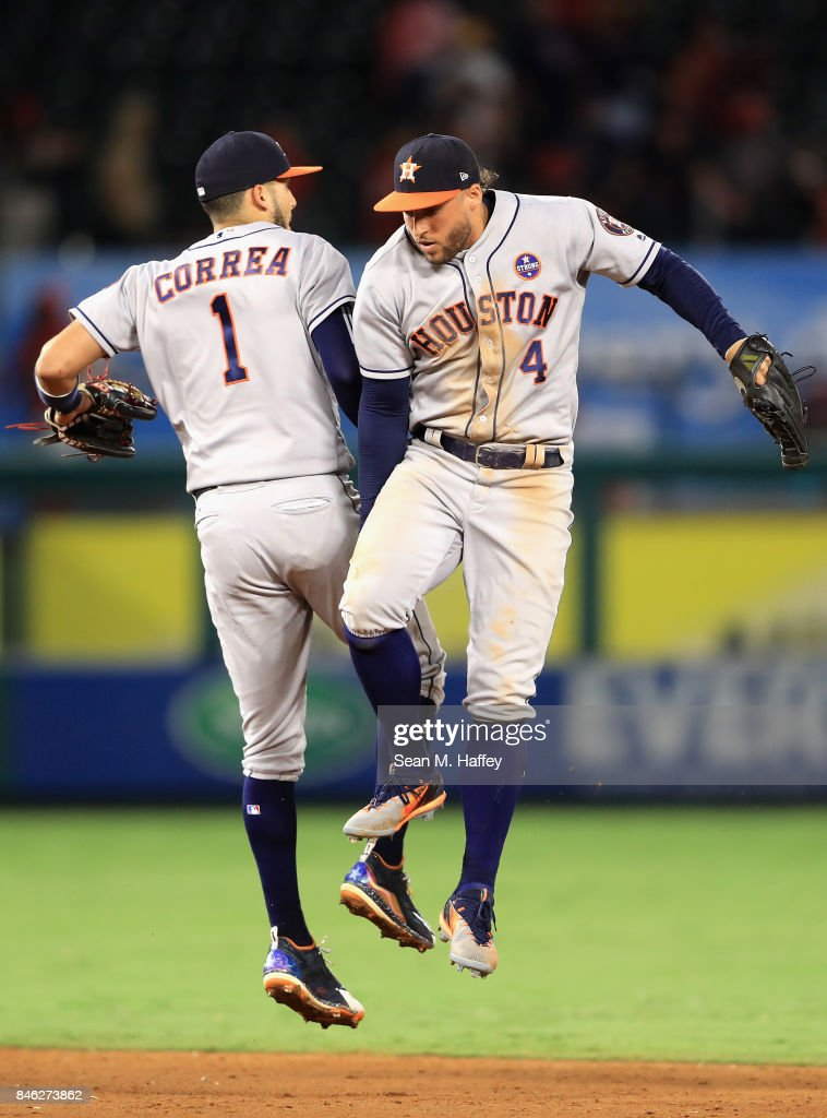 Carlos Correa #1 and George Springer #4 of the Houston Astros celebrate defeating the Los Angeles Angels of Anaheim 1-0 in a game at Angel Stadium of Anaheim on September 12, 2017 in Anaheim, California.