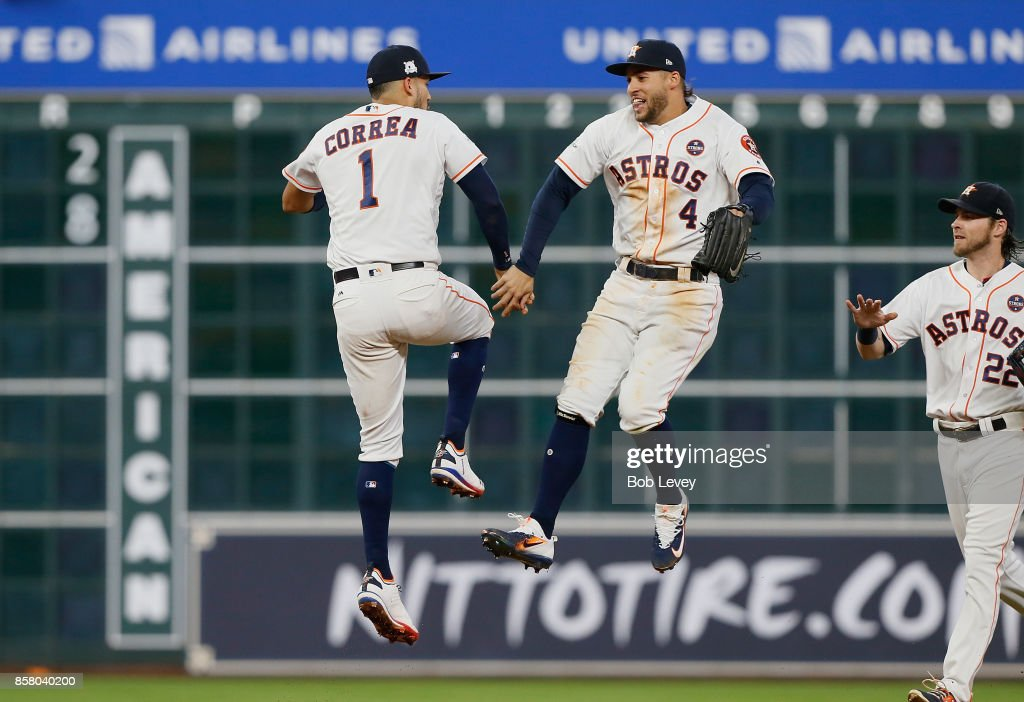 Carlos Correa #1 and George Springer #4 of the Houston Astros celebrate after defeating the Boston Red Sox 8-2 to win game one of the American League Division Series at Minute Maid Park on October 5, 2017 in Houston, Texas.
