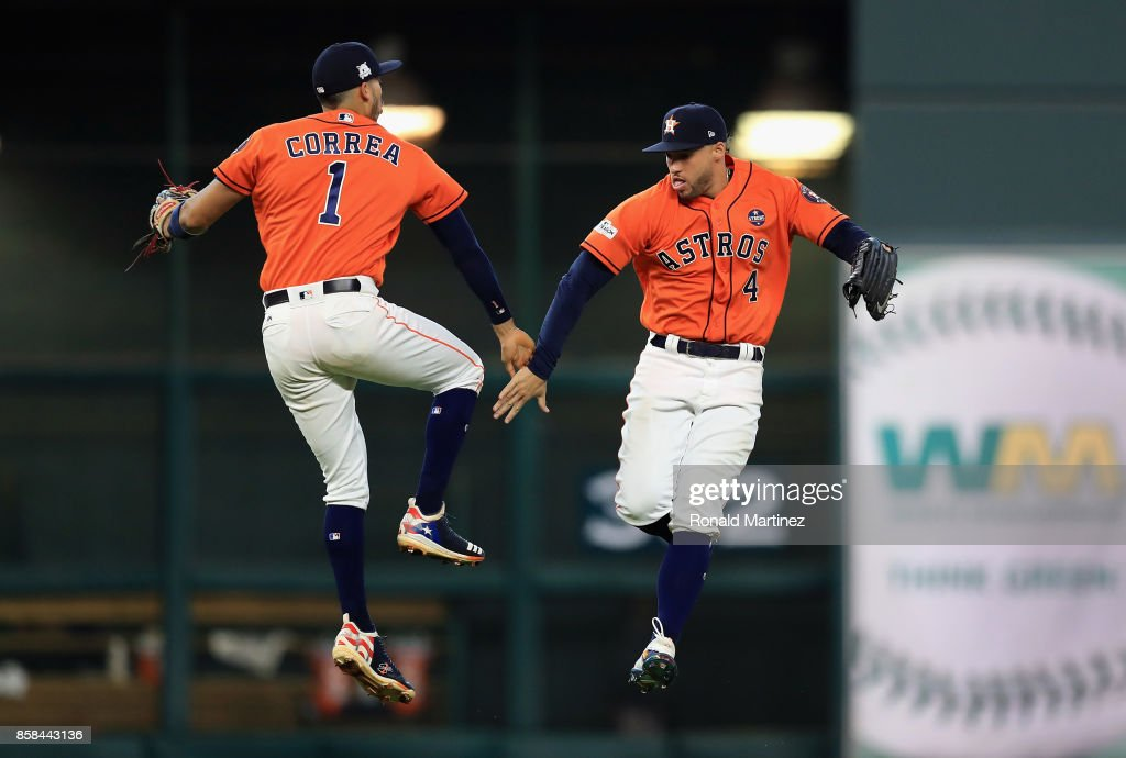 Carlos Correa #1 and George Springer #4 of the Houston Astros celebrate defeating the Boston Red Sox 8-2 in game two of the American League Division Series at Minute Maid Park on October 6, 2017 in Houston, Texas.