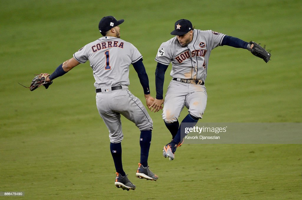 Carlos Correa #1 and George Springer #4 of the Houston Astros celebrate after defeating the Los Angeles Dodgers 7-6 in eleven innings to win game two of the 2017 World Series at Dodger Stadium on October 25, 2017 in Los Angeles, California.