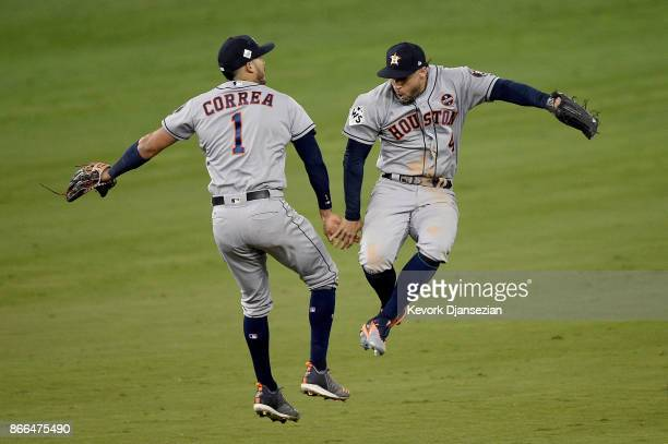 Carlos Correa and George Springer of the Houston Astros celebrate after defeating the Los Angeles Dodgers 7-6 in eleven innings to win game two of...