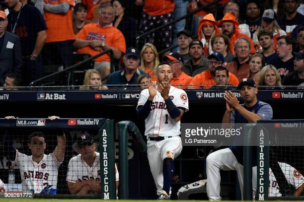 Carlos Correa and hitting coach Alex Cora of the Houston Astros look on from the dugout during Game 3 of the 2017 World Series against the Los...