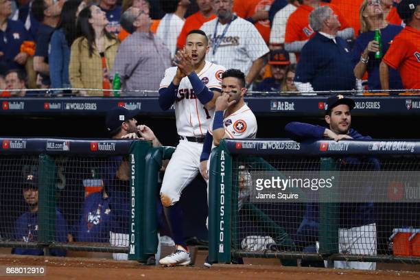Carlos Correa and Jose Altuve of the Houston Astros look on from the dugout against the Los Angeles Dodgers in game five of the 2017 World Series at...