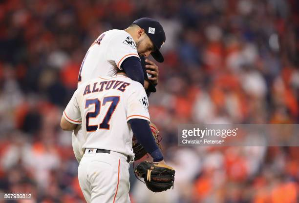Carlos Correa and Jose Altuve of the Houston Astros react as they take the field during the sixth inning against the Los Angeles Dodgers in game five...