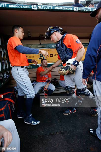 Carlos Correa Jose Altuve and Erik Kratz of the Houston Astros greet each other in the dugout prior to the game against the Oakland Athletics at the...