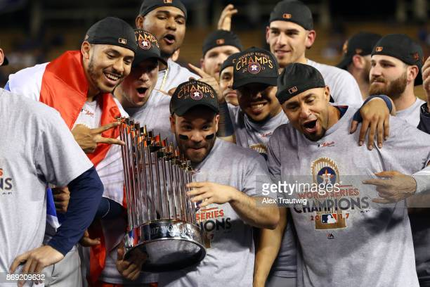 Carlos Correa Jose Altuve of the Houston Astros pose for a photo with the Commissioner's Trophy after the Astros defeated the Los Angeles Dodgers in...