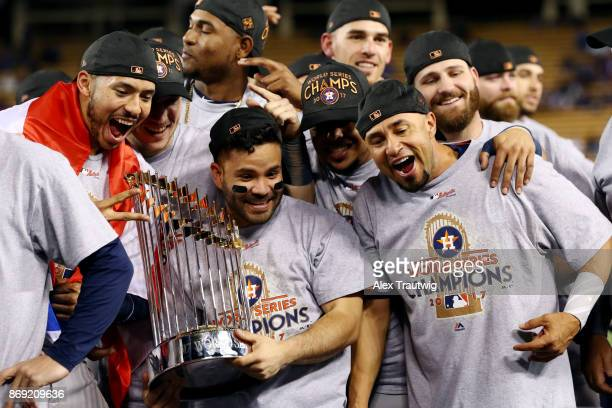 Carlos Correa, Jose Altuve of the Houston Astros pose for a photo with the Commissioner's Trophy after the Astros defeated the Los Angeles Dodgers in...