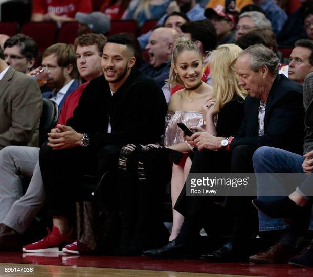 Carlos Correa of the Houston Astros and his fiance Daniella Rodriguez sit courtside with Houston Astros owner Jim Crane and his wife Whitney at...