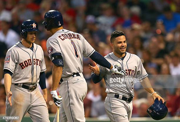 Carlos Correa of the Houston Astros celeberate with Jose Altuve and Alex Presley after they scored in the fourth inning during a game with the Boston...