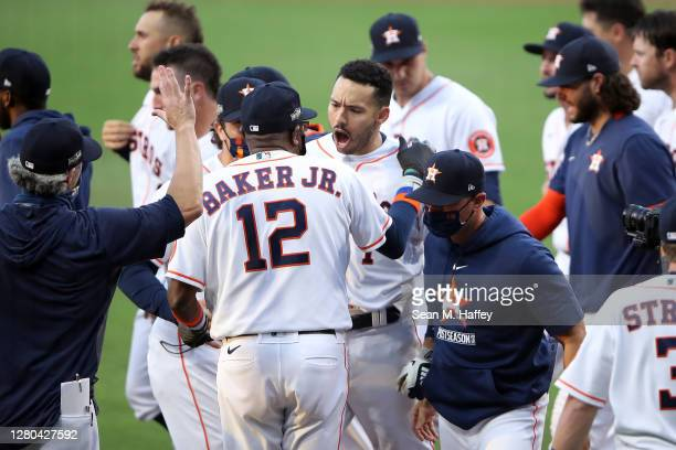 Carlos Correa of the Houston Astros celebrates a walk off home run with manager Dusty Baker against the Tampa Bay Rays in Game Five of the American...