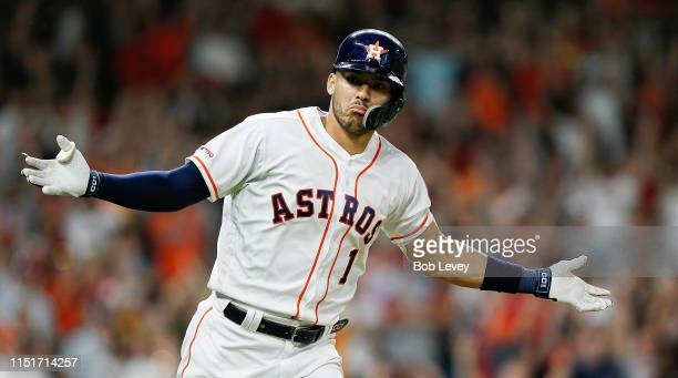 Carlos Correa of the Houston Astros celebrates after hitting a walk off single in the ninth inning against the Boston Red Sox at Minute Maid Park on...