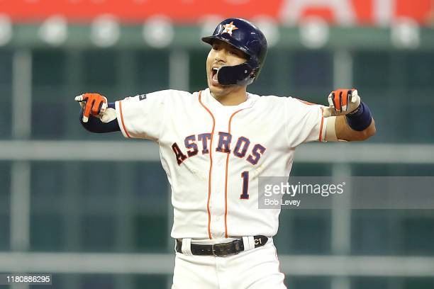 Carlos Correa of the Houston Astros celebrates after hitting an RBI double to score Alex Bregman during the second inning against the New York...