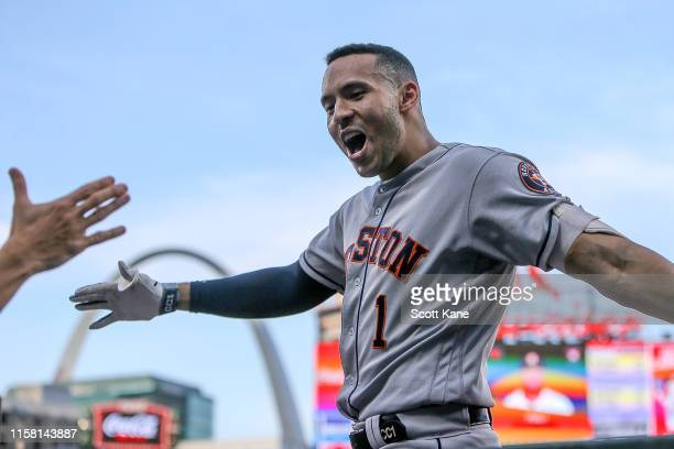 Carlos Correa of the Houston Astros celebrates as he enters the dugout after hitting a grand slam home run during the third inning against the St....