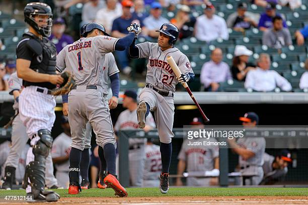 Carlos Correa of the Houston Astros celebrates his first inning tworun home run with teammate Jose Altuve as catcher Nick Hundley of the Colorado...