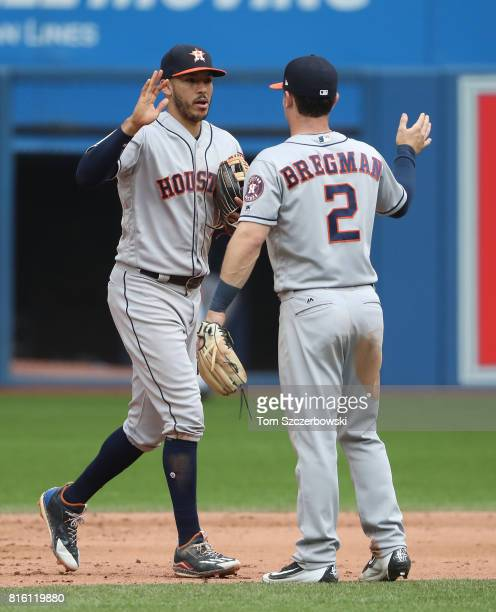 Carlos Correa of the Houston Astros celebrates their victory with Alex Bregman during MLB game action against the Toronto Blue Jays at Rogers Centre...