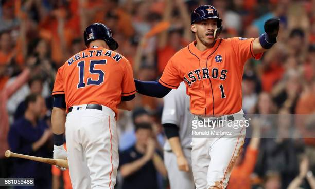 Carlos Correa of the Houston Astros celebrates with Carlos Beltran after scoring on a single by Yuli Gurriel in the fourth inning during game one of...