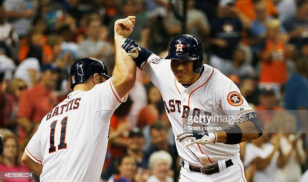 Carlos Correa of the Houston Astros celebrates with Evan Gattis after Correa hit a two-run home run in the sixth inning during their game against the...