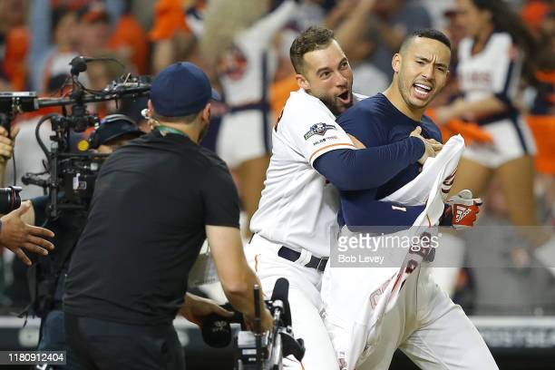 Carlos Correa of the Houston Astros celebrates with George Springer after hitting a walkoff solo home run during the eleventh inning against the New...