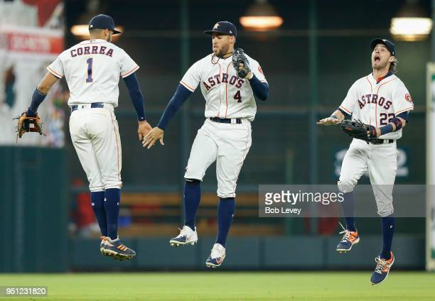 Carlos Correa of the Houston Astros celebrates with George Springer as Josh Reddick looks on after the final out against the Los Angeles Angels of...