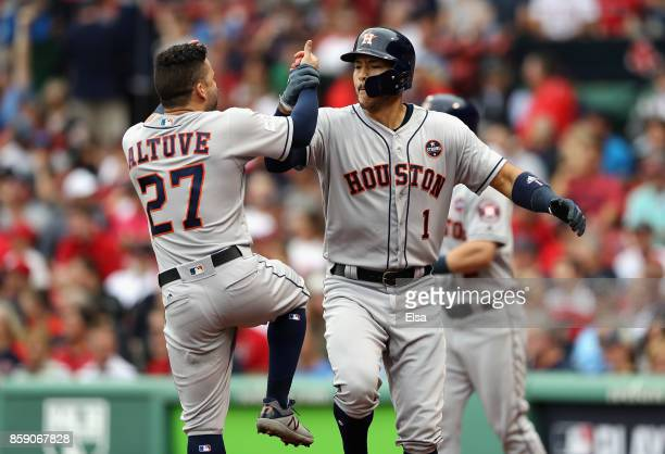 Carlos Correa of the Houston Astros celebrates with Jose Altuve after hitting a tworun home run in the first inning against the Boston Red Sox during...